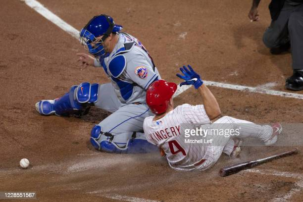 Scott Kingery of the Philadelphia Phillies slides in safely to score a run past Wilson Ramos of the New York Mets in the bottom of the second inning...