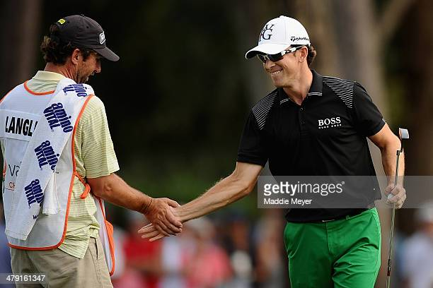 Scott Langley celebrates with his caddie on the 18th green during the final round of the Valspar Championship at Innisbrook Resort and Golf Club on...