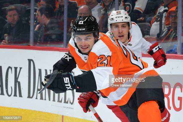 Scott Laughton of the Philadelphia Flyers and Teuvo Teravainen of the Carolina Hurricanes race for the puck in the first period at Wells Fargo Center...