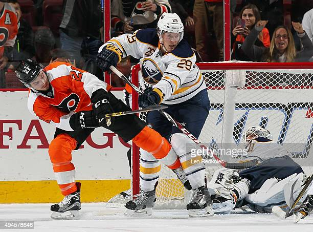 Scott Laughton of the Philadelphia Flyers battles with Jake McCabe of the Buffalo Sabres in front of goaltender Chad Johnson on October 27 2015 at...