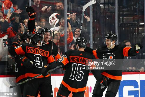 Scott Laughton of the Philadelphia Flyers celebrates his game-winning goal in the third period against the Ottawa Senators with Ivan Provorov, Kevin...