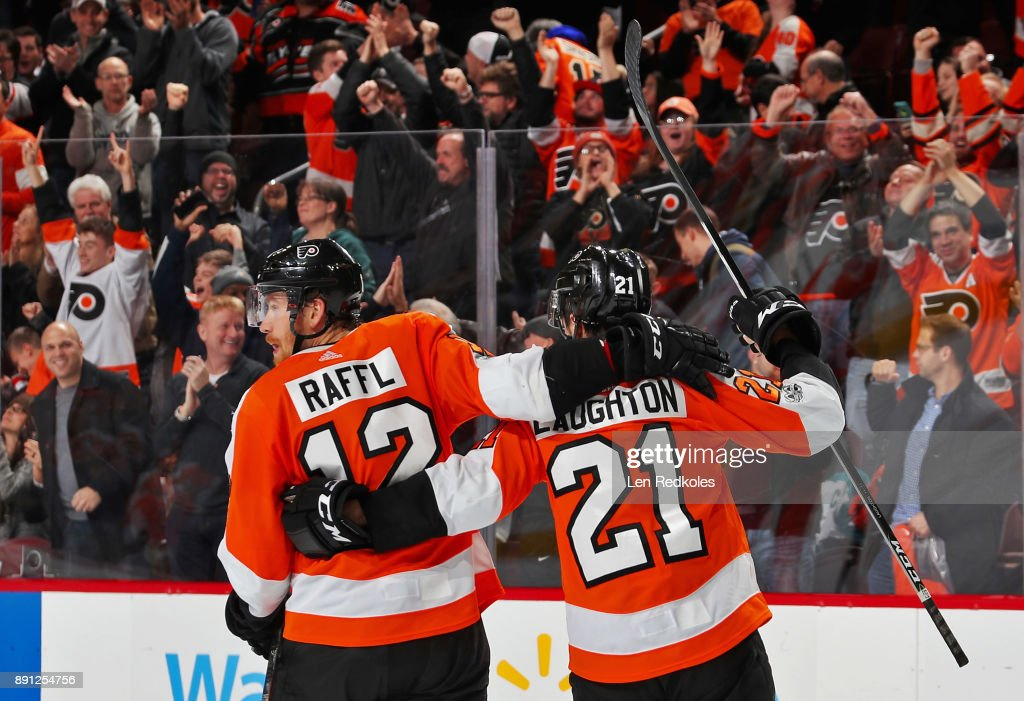 Scott Laughton #21 of the Philadelphia Flyers celebrates his third period empty-net goal against the Toronto Maple Leafs with Michael Raffl #12 on December 12, 2017 at the Wells Fargo Center in Philadelphia, Pennsylvania. The Flyers went on to defeat the Maple Leafs 4-2.