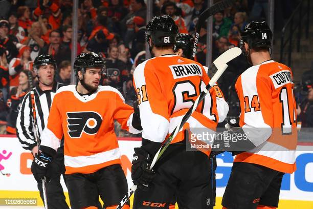Scott Laughton of the Philadelphia Flyers celebrates with Justin Braun and Sean Couturier after scoring a goal against the Winnipeg Jets in the first...