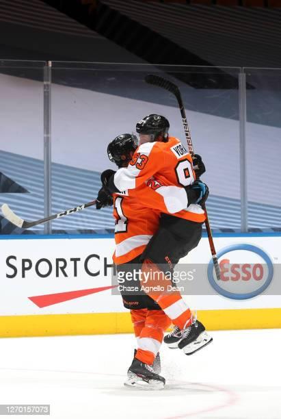 Scott Laughton of the Philadelphia Flyers celebrates with teammate Jakub Voracek after he scored the game winning overtime goal against the New York...