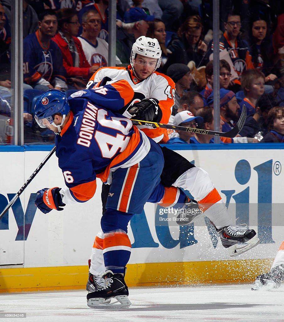 Scott Laughton #49 of the Philadelphia Flyers checks Matt Donovan #46 of the New York Islanders during the first period at the Nassau Veterans Memorial Coliseum on November 24, 2014 in Uniondale, New York.