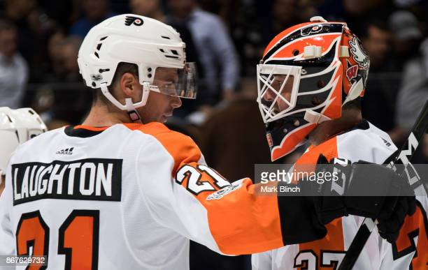 Scott Laughton of the Philadelphia Flyers congratulates goalie Brian Elliott after they defeated the Toronto Maple Leafs at the Air Canada Centre on...