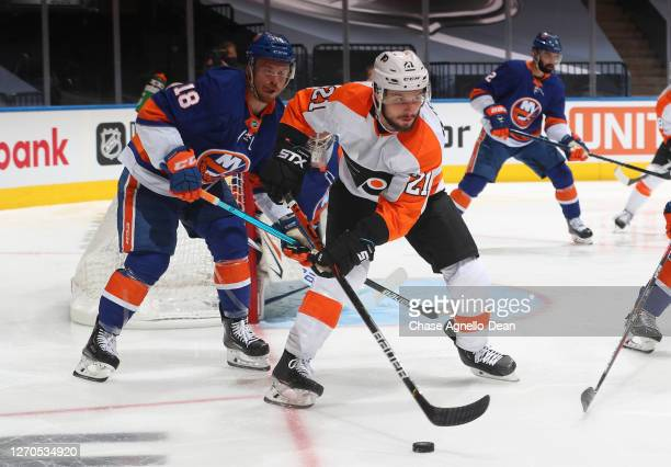 Scott Laughton of the Philadelphia Flyers controls the puck as Anthony Beauvillier of the New York Islanders pursues the play in the third period of...