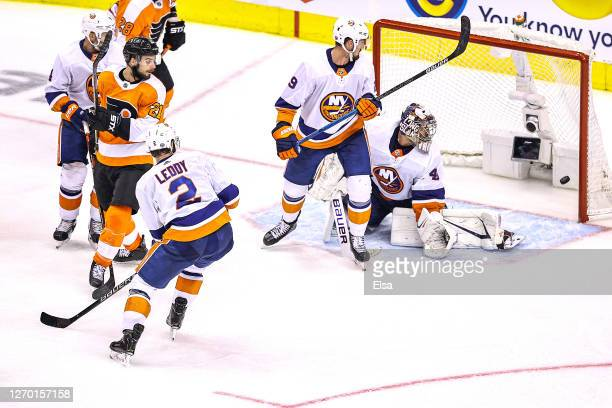 Scott Laughton of the Philadelphia Flyers deflects the shot and scores the game-winning goal past Semyon Varlamov of the New York Islanders during...