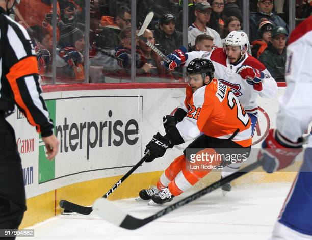 Scott Laughton of the Philadelphia Flyers handles the puck in the corner against Victor Mete of the Montreal Canadiens on February 8 2018 at the...
