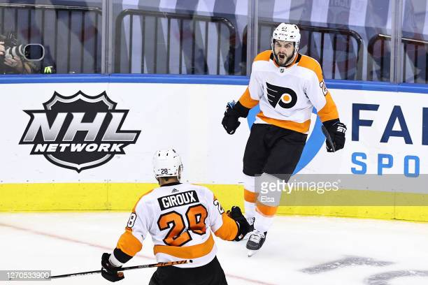 Scott Laughton of the Philadelphia Flyers is congratulated by his teammate, Claude Giroux after scoring a goal against the New York Islanders during...