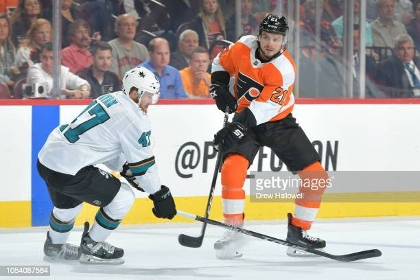 Scott Laughton of the Philadelphia Flyers passes around Joakim Ryan of the San Jose Sharks at the Wells Fargo Center on October 9 2018 in...