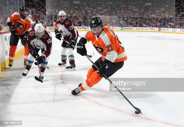 Scott Laughton of the Philadelphia Flyers skates the puck against Sven Andrighetto and Alexander Kerfoot of the Colorado Avalanch on October 22 2018...
