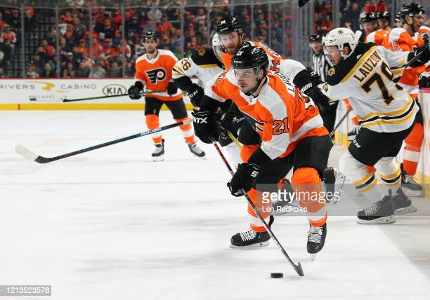 Scott Laughton of the Philadelphia Flyers skates the puck with Sean Couturier against Jeremy Lauzon of the Boston Bruins on March 10 2020 at the...