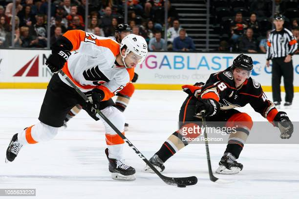 Scott Laughton of the Philadelphia Flyers skates with the puck with pressure from Isac Lundestrom of the Anaheim Ducks during the game on October 30...