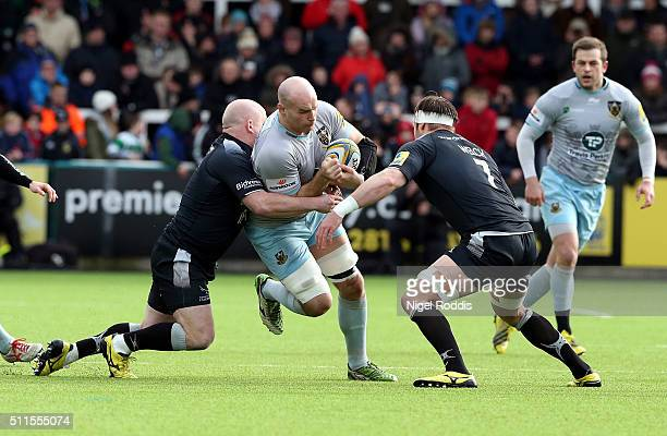 Scott Lawson and Will Welch of Newcastle Falcons tackle Sam Dickinson of Northampton Saints during the Aviva Premiership match between Newcastle...