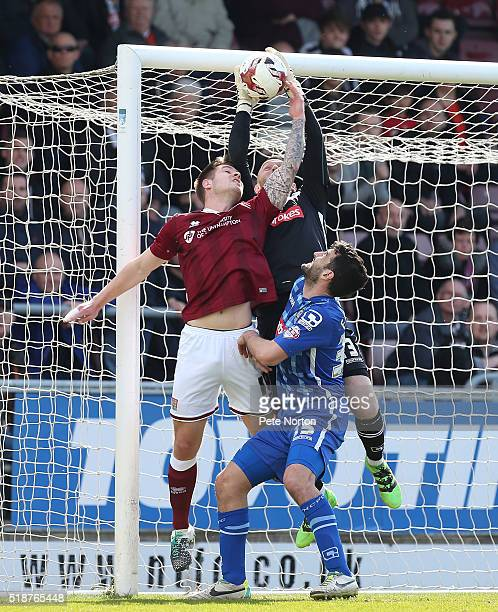 Scott Loach of Notts County collects the ball under pressure from James Collins as yeam mate Mike Edwards looks on during the Sky Bet League Two...