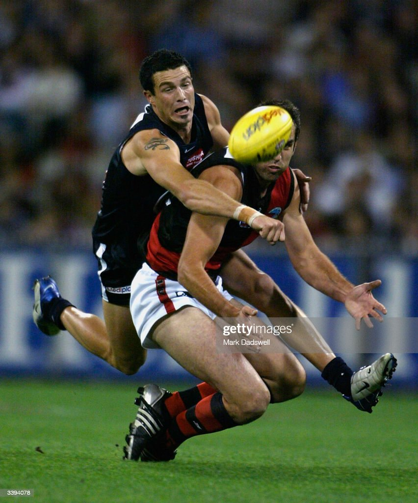 Scott Lucas #25 for the Bombers is spoiled by Karl Norman #37 for the Blues during the round four AFL match between the Carlton Blues and the Essendon Bombers at the Melbourne Cricket Ground April 16, 2004 in Melbourne, Australia.