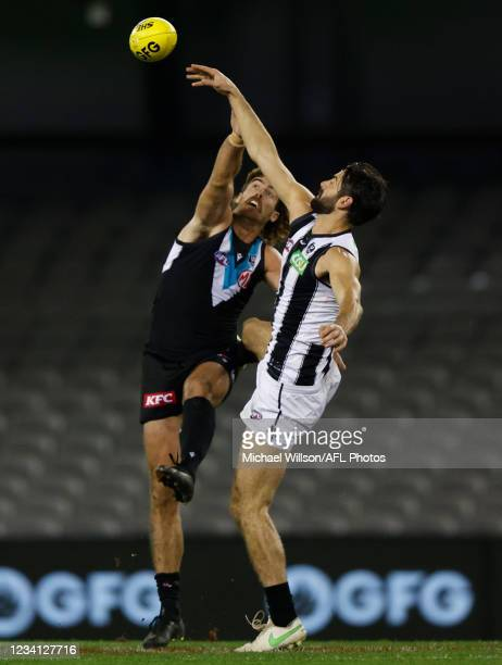 Scott Lycett of the Power and Brodie Grundy of the Magpies compete in a ruck contest during the 2021 AFL Round 19 match between the Port Adelaide...