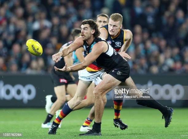 Scott Lycett of the Power handpasses the ball away from Reilly O'Brien of the Crows during the 2021 AFL Round 08 match between the Port Adelaide...