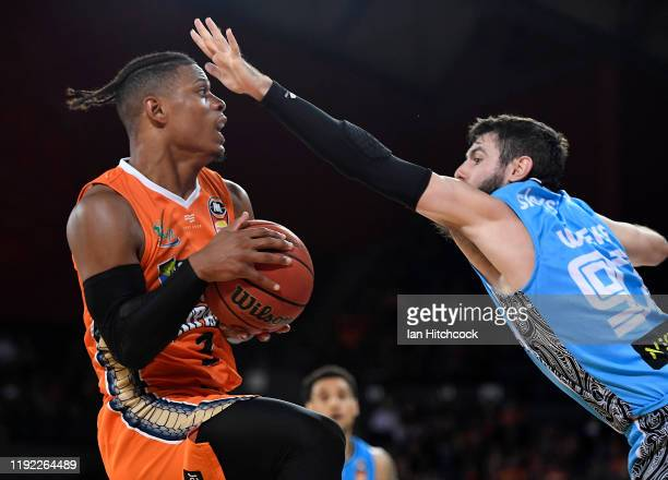 Scott Machado of the Taipans attempts a lay up past Jarrad Weeks of the Breakers during the round 10 NBL match between the Cairns Taipans and the New...