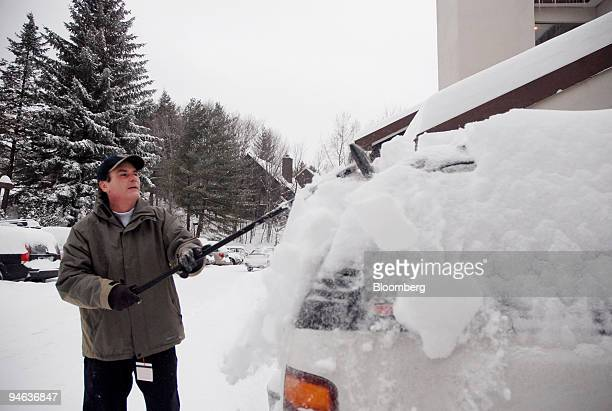 Scott Madsen of Whippany New Jersey cleans snow off his car near his home in Warren Vermont US on Sunday Dec 17 2007 A nor'easter is forecast to...