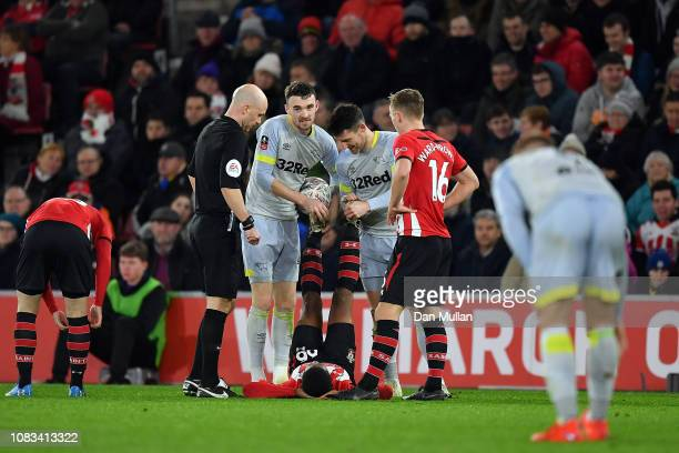Scott Malone and David Nugent of Derby County help Kayne Ramsay of Southampton with cramp during the FA Cup Third Round Replay match between...
