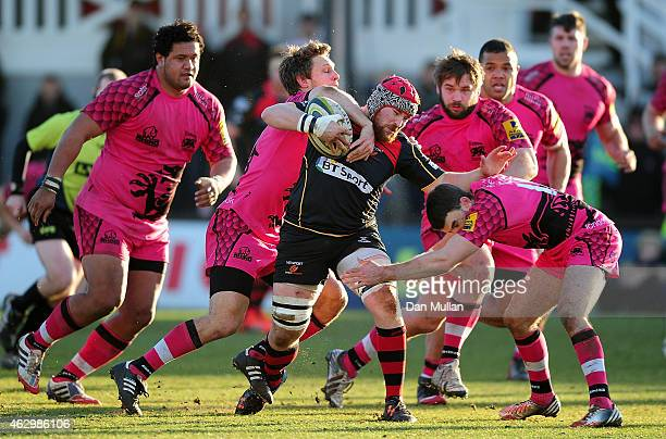 Scott Matthews of the Dragons is tackled by Nic Reynolds and Nick Scott of London Welsh during the LV= Cup match between Newport Gwent Dragons and...