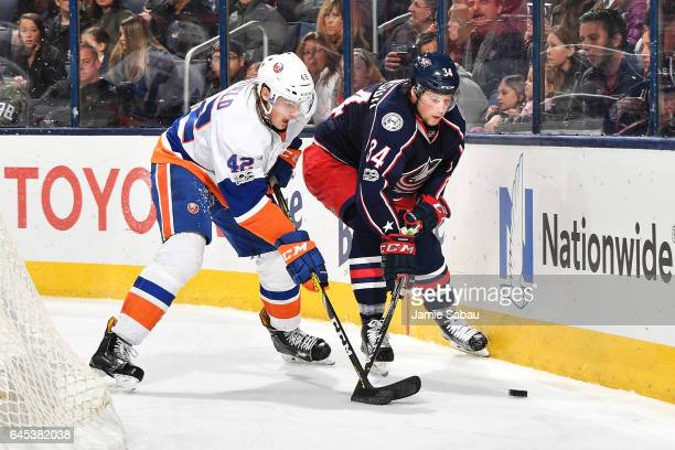Scott Mayfield of the New York Islanders and Josh Anderson of the Columbus Blue Jackets battle for a loose puck during the third period of a game on...