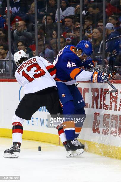 Scott Mayfield of the New York Islanders and Nico Hischier of the New Jersey Devils battle for the puck along the boards during the second period at...