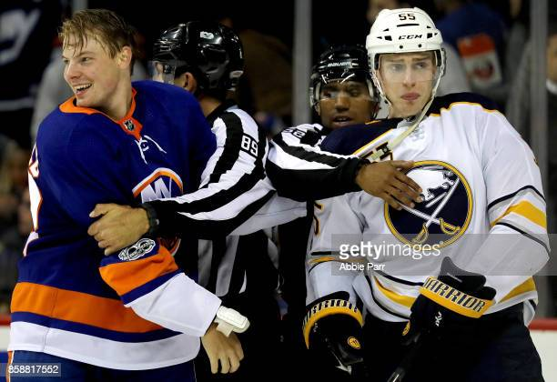 Scott Mayfield of the New York Islanders and Rasmus Ristolainen of the Buffalo Sabres react after getting into a fight during the second period at...