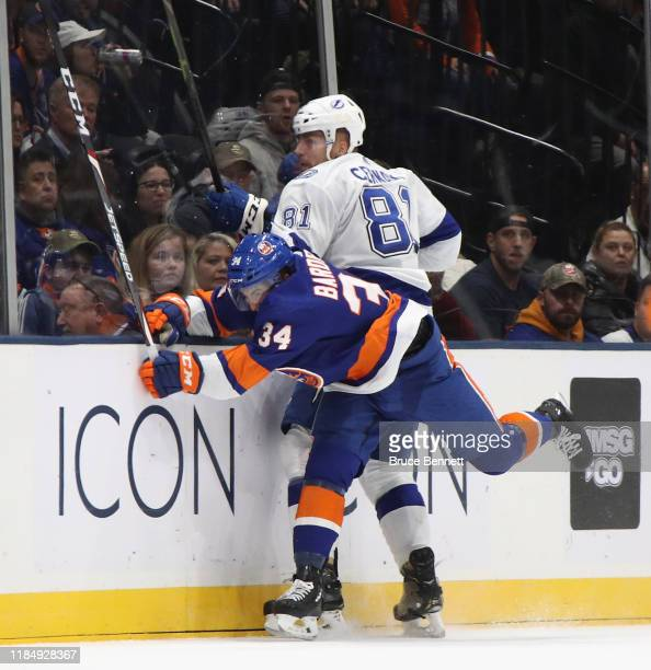 Scott Mayfield of the New York Islanders checks Erik Cernak of the Tampa Bay Lightning during the first period at NYCB Live's Nassau Coliseum on...