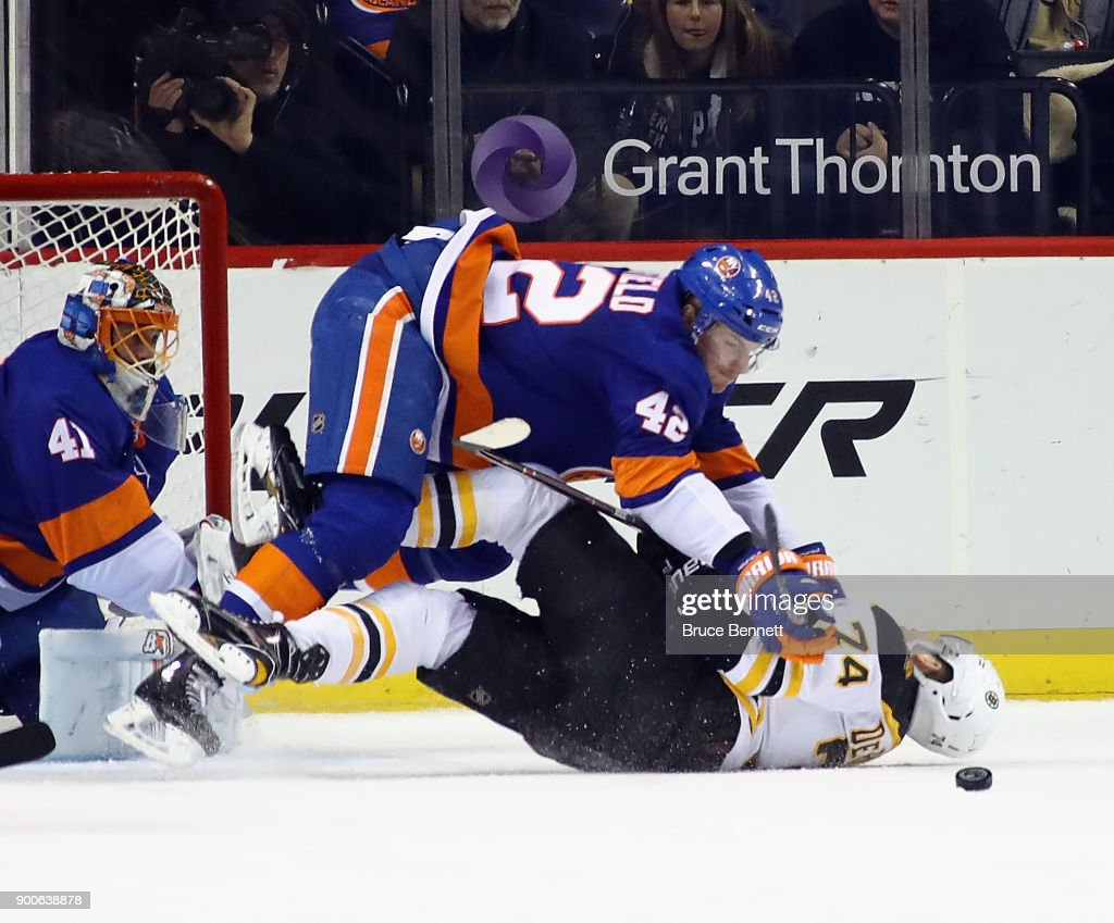Scott Mayfield #42 of the New York Islanders checks Jake DeBrusk #74 of the Boston Bruins during the second period at the Barclays Center on January 2, 2018 in the Brooklyn borough of New York City.
