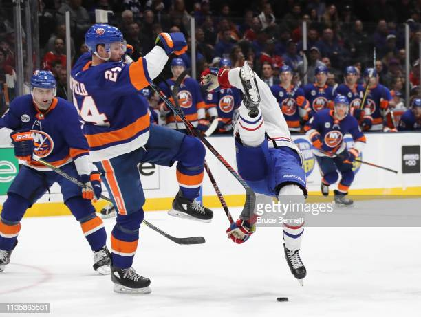 Scott Mayfield of the New York Islanders checks Jesperi Kotkaniemi of the Montreal Canadiens during the third period at NYCB Live's Nassau Coliseum...