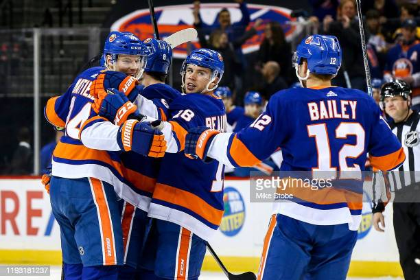 Scott Mayfield of the New York Islanders is congratulated by his teammates after scoring a goal against the Boston Bruins during the first period at...