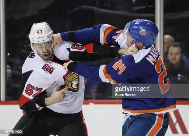 Scott Mayfield of the New York Islanders lands a punch on Ben Harpur of the Ottawa Senators at the end of the third period at the Barclays Center on...
