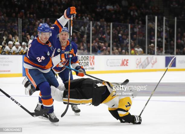 Scott Mayfield of the New York Islanders trips up Evgeni Malkin of the Pittsburgh Penguins during the first period at NYCB Live at the Nassau...