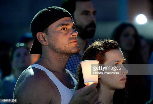 Scott McCullough and Hanna Marchetti of Portland stand together during a candlelight vigil at Monument Square that was part of the International...
