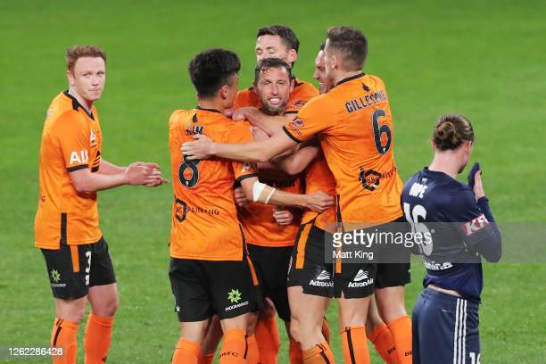 Scott McDonald of the Roar celebrates with team mates after scoring a goal during the round 24 A-League match between the Melbourne Victory and the...