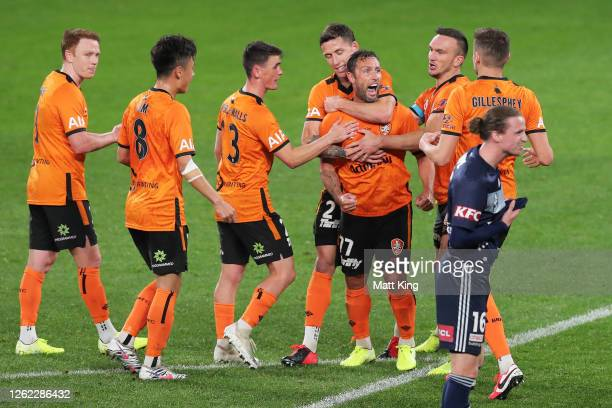 Scott McDonald of the Roar celebrates with team mates after scoring a goal during the round 24 ALeague match between the Melbourne Victory and the...