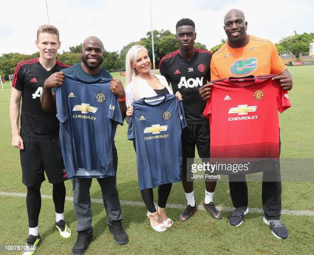 Scott McTominay and Axel Tuanzebe of Manchester United pose with WWE wrestlers Apollo Crews, Dana Brooke and Titus O'Neil after a training session as...