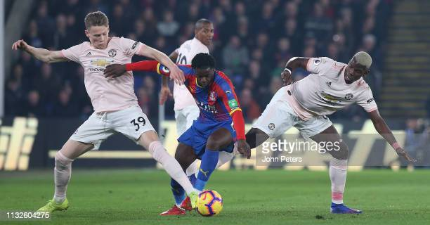 Scott McTominay and Paul Pogba of Manchester United in action with Jeffrey Schlupp of Crystal Palace during the Premier League match between Crystal...