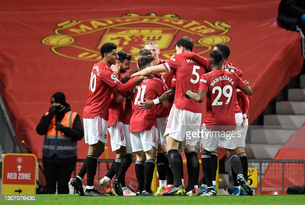 Scott McTominay of Manchester United celebrates with Bruno Fernandes and team mates after their side's first goal, an own goal scored by Craig Dawson...