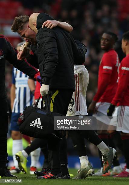 Scott McTominay of Manchester United is helped off the pitch during the Premier League match between Manchester United and Brighton Hove Albion at...