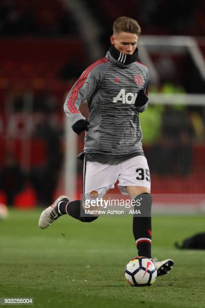 Scott McTominay of Manchester United wears a hat and snood in the cold weather whilst warming up during the FA Cup Quarter Final match between...