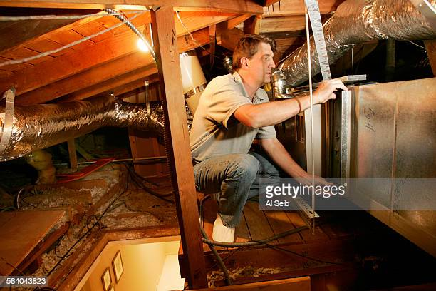 GLENDALE CA Scott Menzel a Mechanical Engineer with George Haney and Son Inc a Carrier Heating and Air Conditioning contractor prepares the attic...