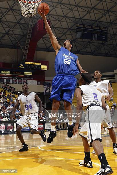 Scott Merritt of the Dallas Mavericks drives to the hoop against Pape Sow and Greg Logan of the Toronto Raptors at the Southern California Summer Pro...