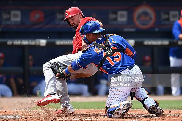 Scott Moore of the St Louis Cardinals is tagged out at home plate by Johnny Monell of the New York Mets during the second inning of a spring training...