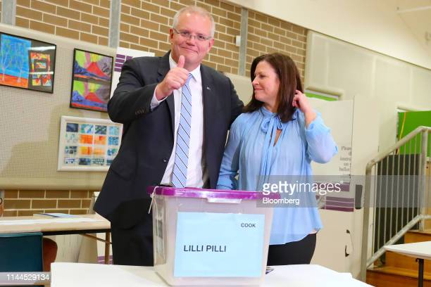 Scott Morrison Australia's prime minister left gestures a thumbs up while standing next to wife Jenny Morrison after casting his ballot at a polling...