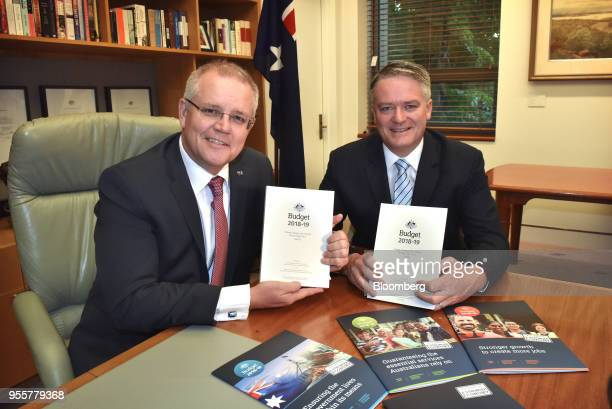 Scott Morrison Australia's treasurer left and Mathias Cormann Australia's finance minister hold copies of the federal budget while posing for a...
