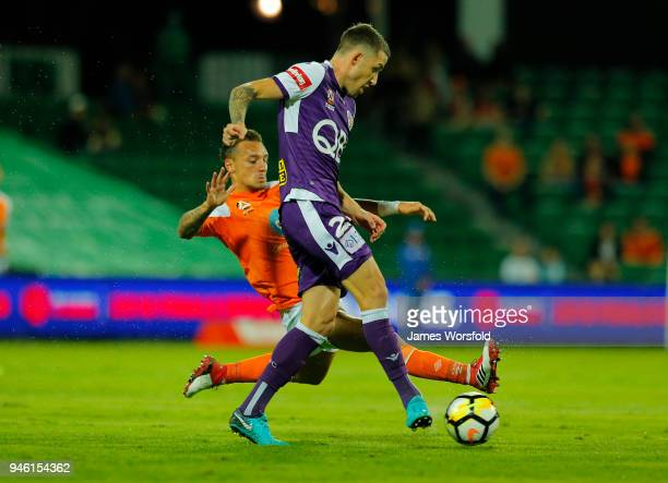 Scott Neville of the Perth Glory pass the ball away while under pressure from Eric Bautheac of the Brisbane Roar during the round 27 ALeague match...